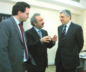 Christos Pachtas (center) talking to Yiannos Papantoniou (right), former PASOK Minister of Finance and Defence, currently implicated in mismanagement scandal. Giorgos Papakonstantinou looks on. (photo via epoxeschannel.blogspot.com)